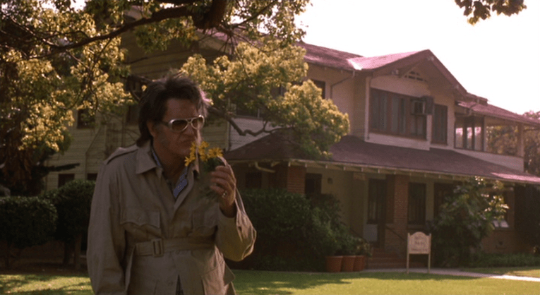 Screencap from Bubba Ho-Tep: An older Elvis stands in front of a two story craftsman house, holding a flower.