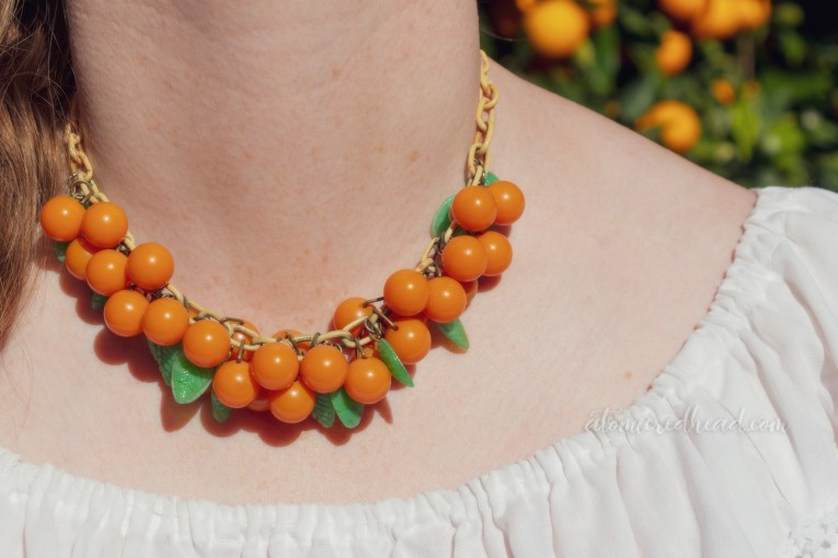 Close-up of my necklace, small orange balls hang on a plastic chain with small plastic green leaves.