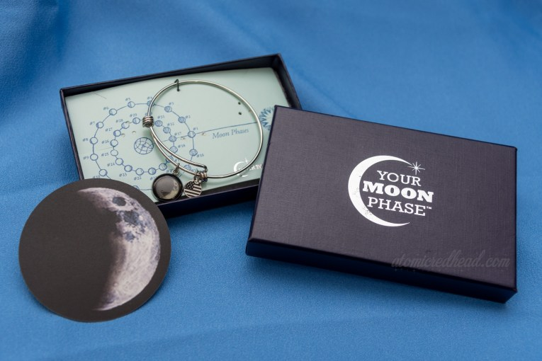 Moon Phase bracelet in box, a slim silver circle with a charm featuring a crescent moon design on it.