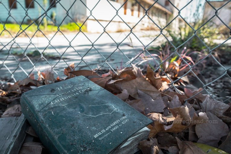 A molding copy of California's Health and Safety Code sits in a pile of leaves by a chainlink fence.