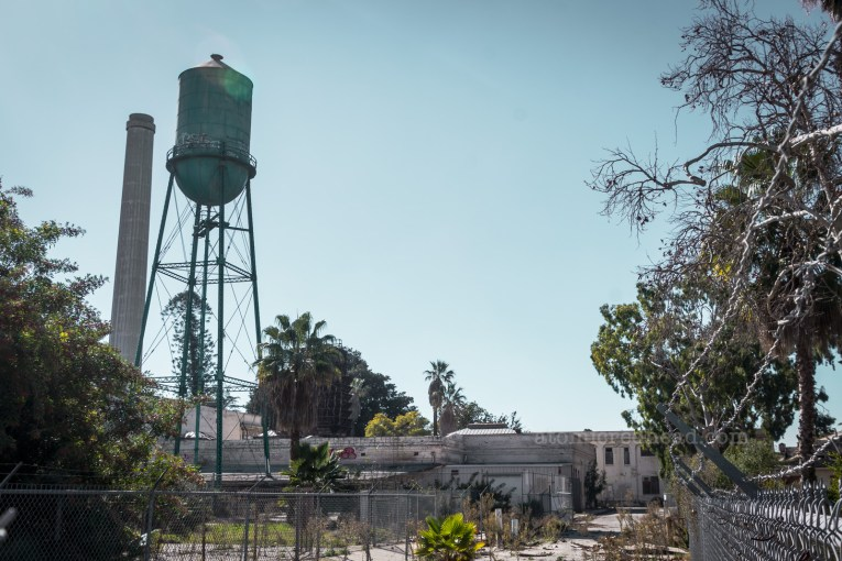 A tall water tower stands next to a smokestack.