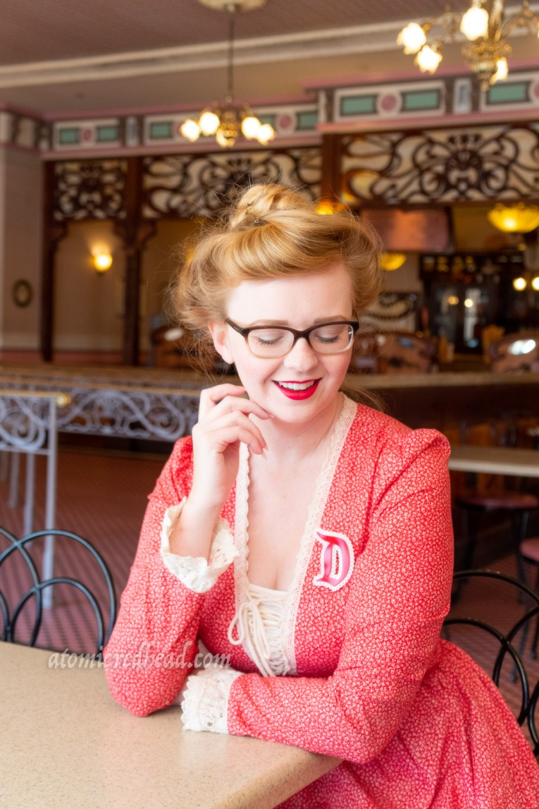 "Myself, sitting inside the Gibson Girl Ice Cream Parlor, wearing a long, red dress with a small floral pattern, with lace trim at the laced V-neckline, and cuffs. A red ""D"" brooch edged in white is worn on my left shoulder, my hair in a Gibson Girl updo."