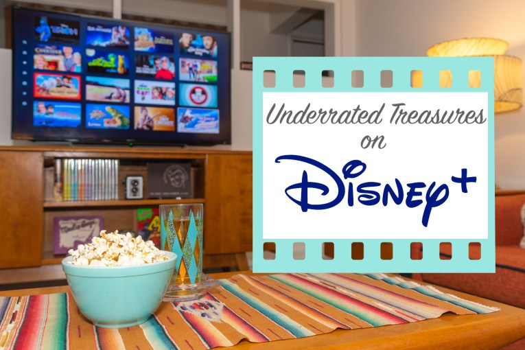 "A bowl of popcorn sits on a coffee table, the TV is on the background with various movie titles on it from Disney+. Text on top reads ""Underrated Treasures on Disney+"""