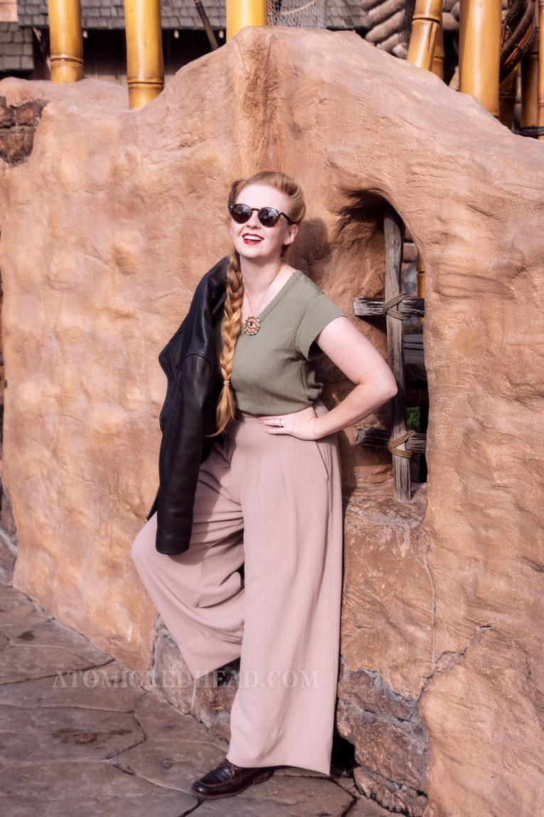 Myself, wearing an olive green peasant top, a necklace with an image of a ruby eye hangs from my neck, and wide leg khaki pants, my leather jacket slung over my shoulder, standing in front of an old adobe wall.