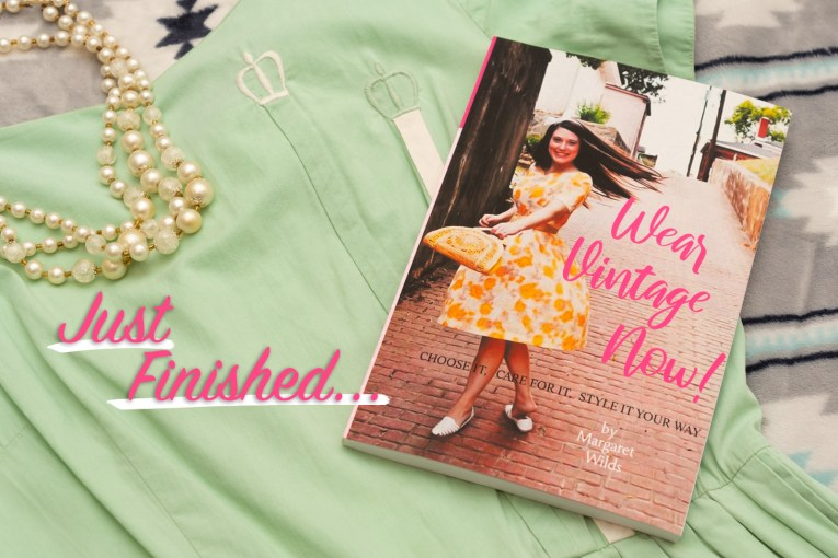 "A book titled ""Wear Vintage Now"" with a girl in an orange and yellow dress twirls on the cover, sits on a green dress with crowns embroidered on it a strand of pearls lays across the neckline. Pink text overlay reads ""Just Finished..."""