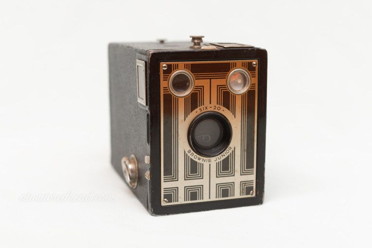 Kodak Brownie Junior Six-20. A black box style camera with a metal plate in front featuring a black and gold deco design.