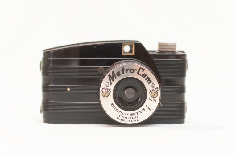 "Metro Cam. A small black rangefinder style camera. Around the lens is a small silver metal plate reading ""Metro Cam"" with scroll detailing."