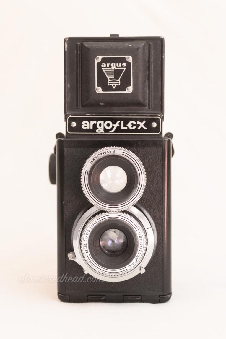 "Argoflex E. A black dual lens camera with silver trim around the lenses. Silver text across the top reads ""Argoflex"""