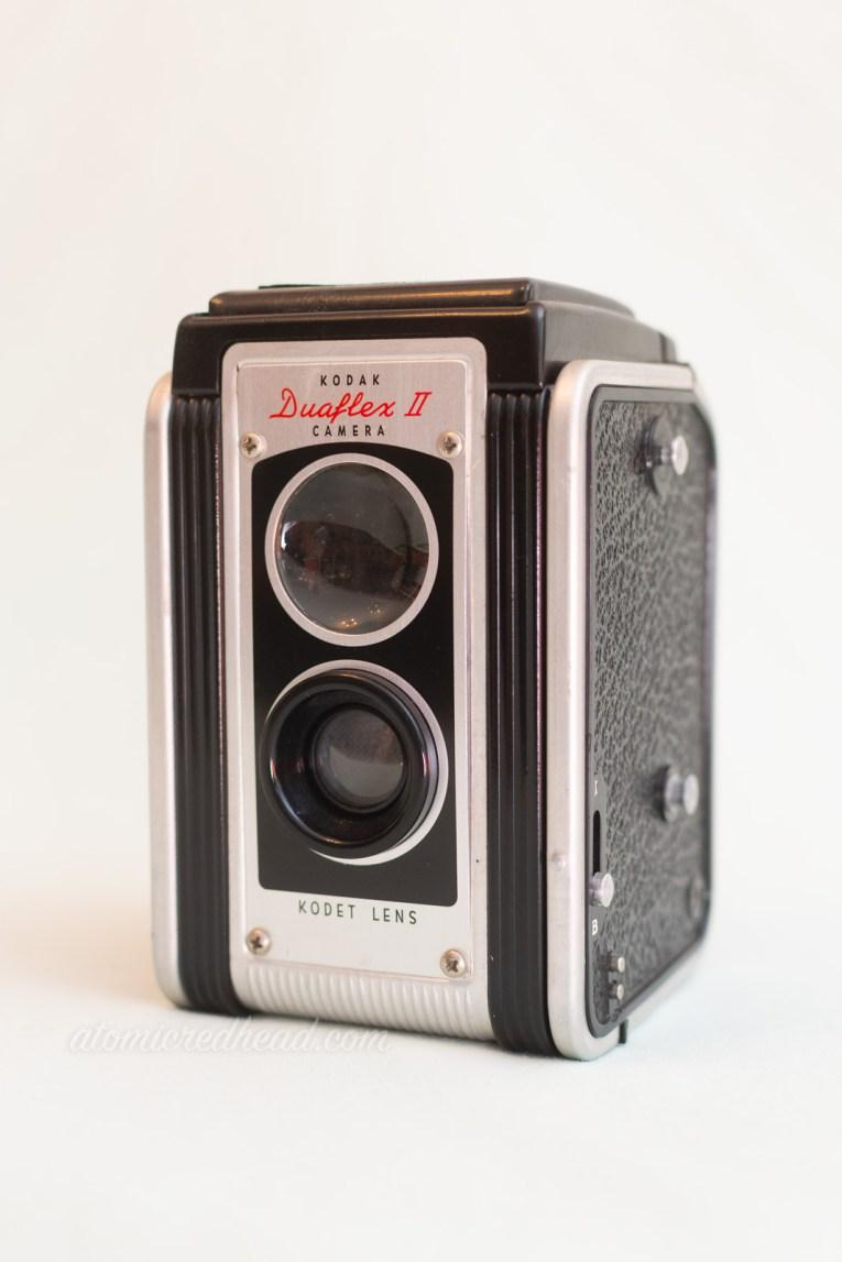 """Kodak Duaflex II. A silver and black dual lens camera. Red script at the top reads """"Duaflex II"""""""