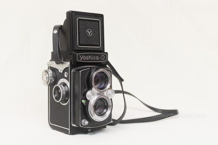 Yashica-D. A black dual lens camera with silver trim around the lenses and some dials.