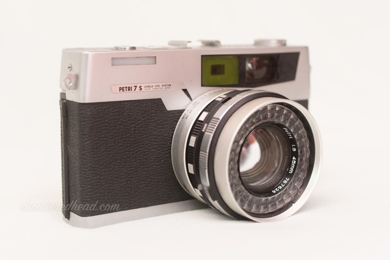 Petri 7S. A black and silver rangefinder type camera with the flash built into the lens.