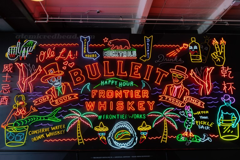 "A massive neon mural for Bulleit Whiskey. Various images of a mermaid in a glass, a skeleton in a suit, palm tree, a shirtless man in a cowboy hat in a glass, a shark mouth with a taco inside, legs, California Bear, and various text reading ""Bulleit Frontier Whiskey,"" ""Conserve Water Drink Whiskey,"" ""Cocktails,"" ""Drinks,"" ""After Hours,"" and ""Old Soul, Fresh Times"""