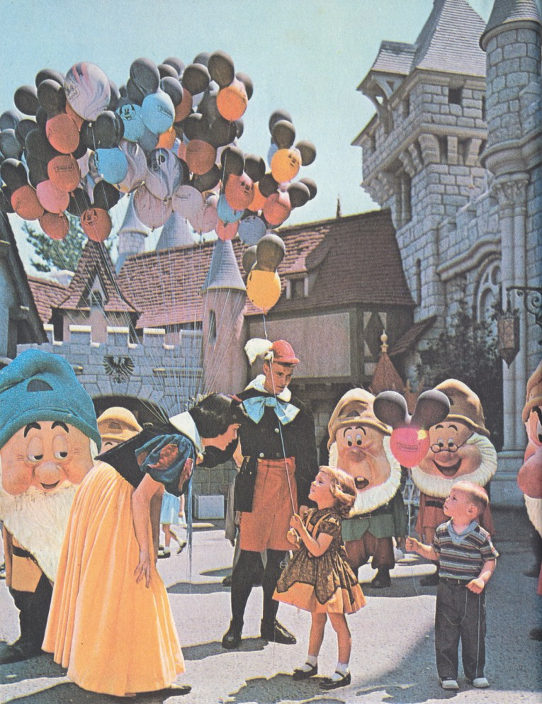 Photograph of Snow White with her seven dwarf friends, and a man holding balloons near Sleeping Beauty Castle.
