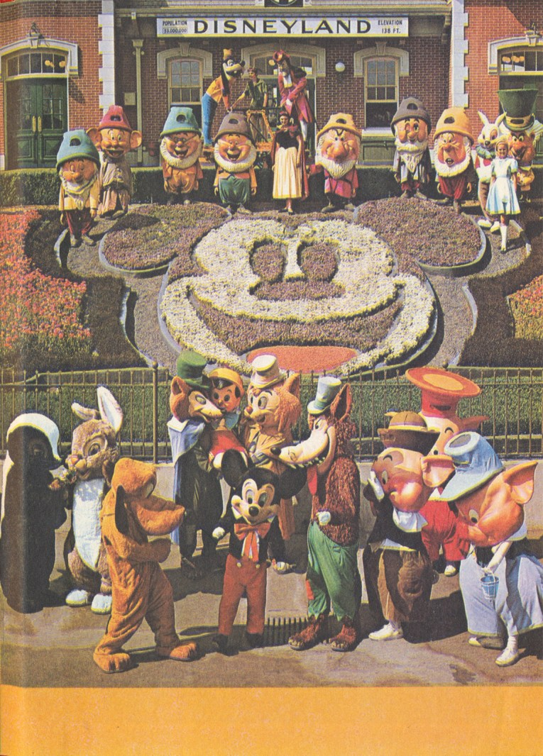 Photo of Mickey and many costumed characters in front of the large floral Mickey by the Train Station