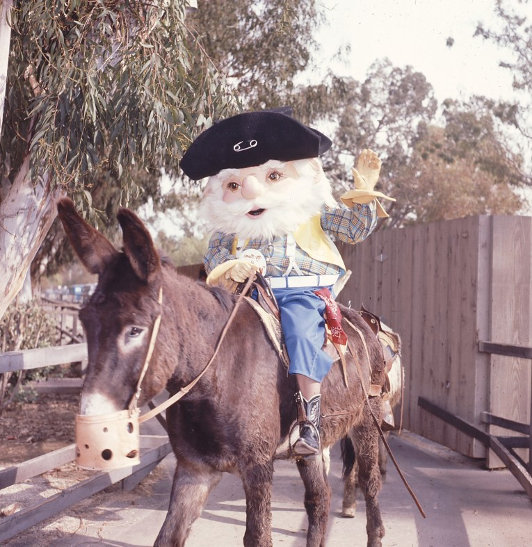 "An awkwardly proportioned old miner in the form of a fuzzy mascot costume, he has a white beard, black hat, plaid shirt with yellow vest, and blue jeans. He wears a button reading ""My name is...Whittles'"" rides a donkey"