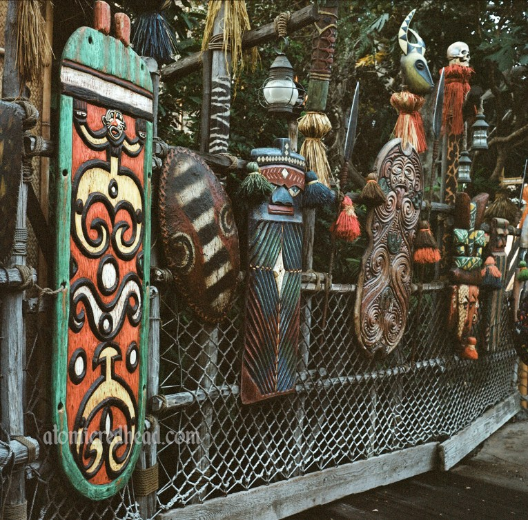 Various colorful masks, spears, and shields of Adventureland.