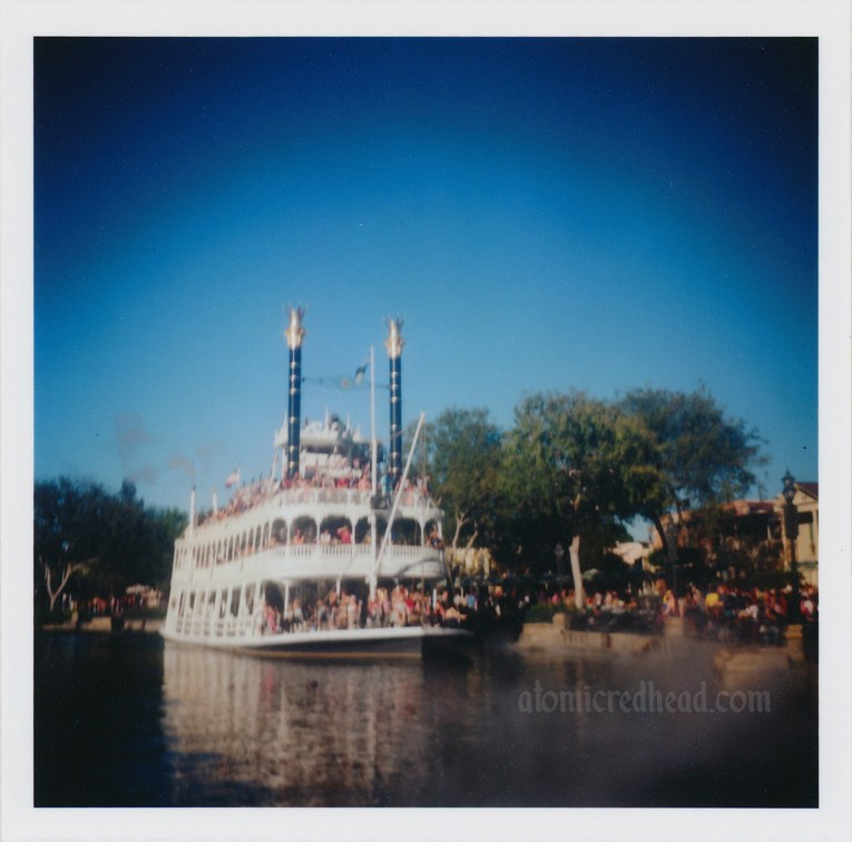 The Mark Twain Riverboat, a white, old fashioned paddle wheeler churns through the Rivers of America.