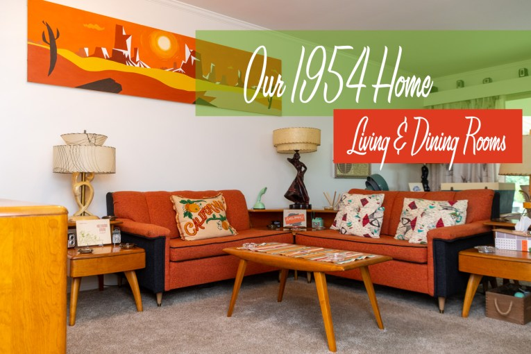 "Two orange and black sofas sit in an L shape. A painting above one sofa features a modern desert landscape. A pillow on one sofa reads ""California"" and features oranges on it. Pillows on the other sofa are abstract modern designs of maroon and teal. A square, step table sits between the two sofas. Text overlay reads ""Our 1954 Home Living & Dining Rooms"""