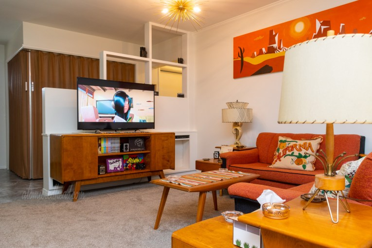 View toward our TV. A television sits atop a warm wood credenza in front of it are two sofas in an L shape. They are upholstered in orange and black fabric. A coffee table of the same wood sits in front. Step end tables of the same wood flank the sofas.