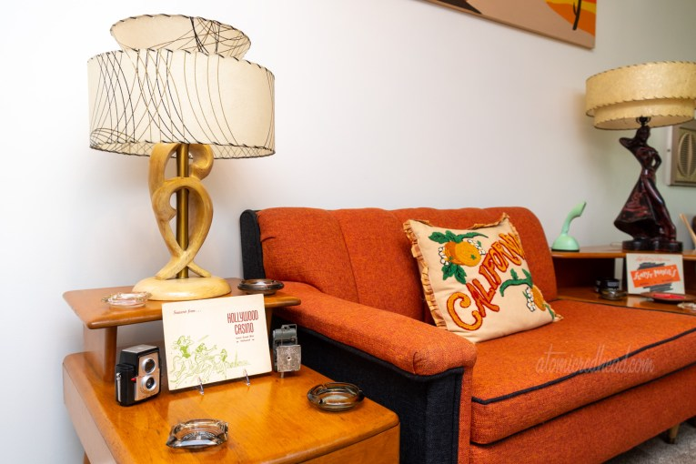 "A warm wood step end table sits aside a sofa of orange and black fabric. On the end table is a lamp, two vintage cameras, and a photo folder for a Hollywood night club. On the sofa is a pillow reading ""California"" with oranges on it."