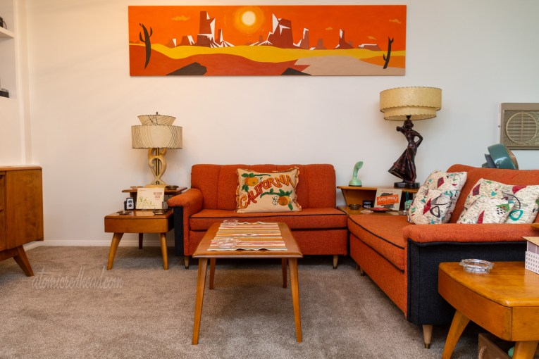 "Two orange and black sofas sit in an L shape. A painting above one sofa features a modern desert landscape. A pillow on one sofa reads ""California"" and features oranges on it."