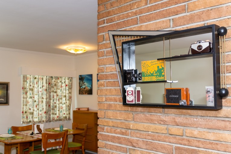 A modern abstract shaped shadow box hangs on a brick fireplace. Cameras sit inside the shadowbox.