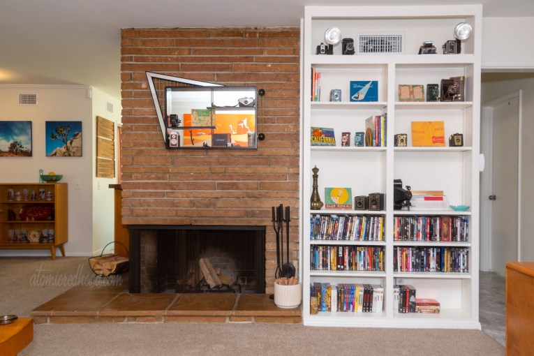 On the left is our fireplace, with a shadowbox hanging above it. On the right is a built in book shelf with books, DVDs, and vintage cameras sitting on it.