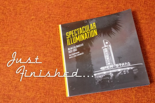 "Cover of Spectacular Illumination, which features a black and white photograph of a streamline modern drive-in restaurant. Overlay text on the photo reads ""Just Finished..."""