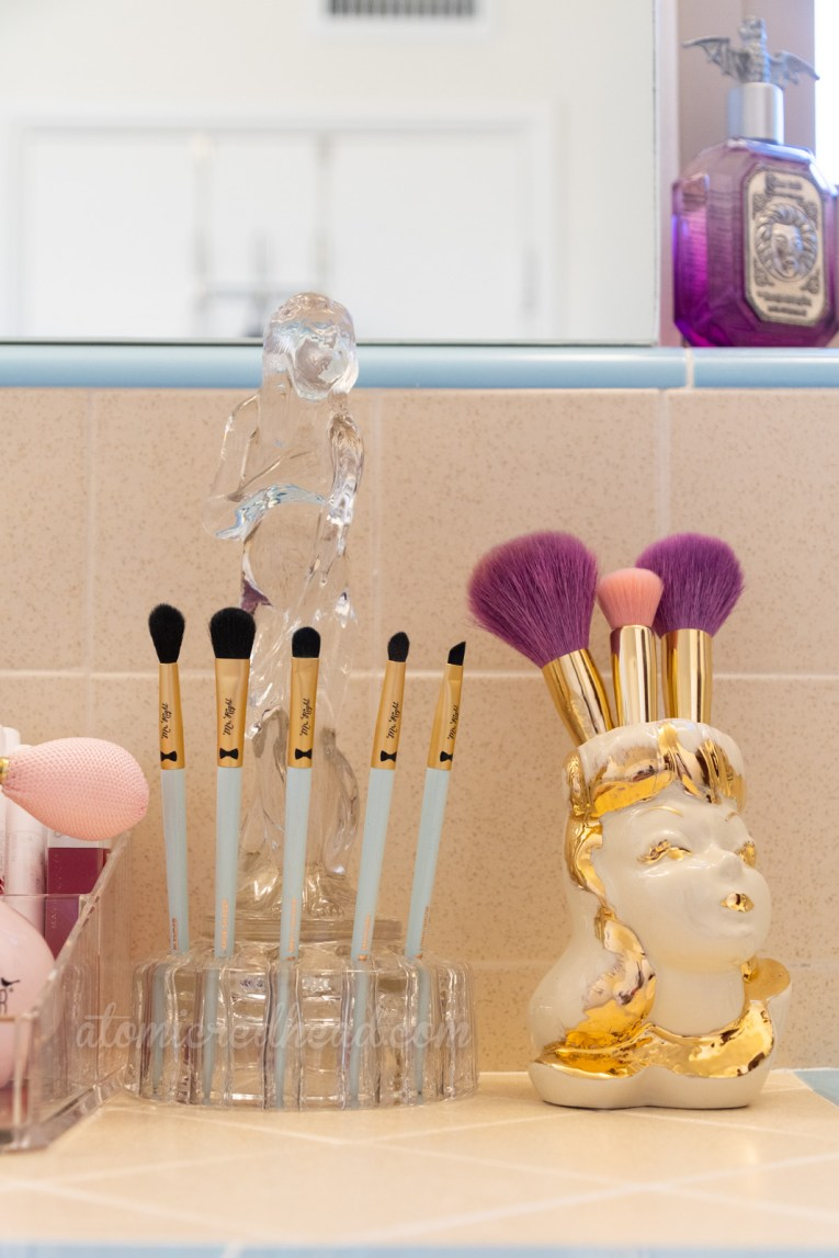 A glass figure of a woman features a base with small holes along it, which allow make-up brushes to fit in perfectly. Next to her a ceramic vase of a woman's head holds larger make-up brushes.