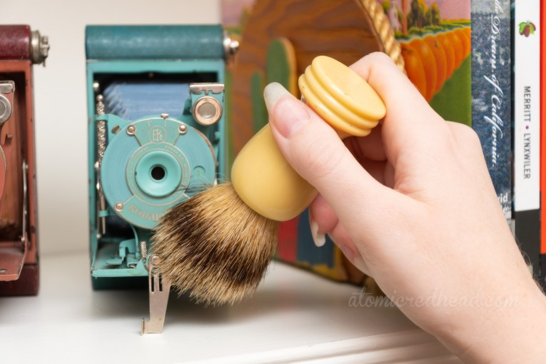 A hand enters the frame from the right with an old shaving brush, it is being used to dust an old camera.