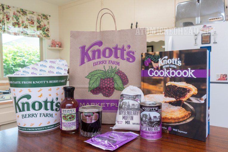 "A bag reading ""Knott's Berry Farm"" with a cluster of boysenberries sits in the middle, it is surrounded by a bucket of chicken, boysenberry vinaigrette, boysenberry jam, a baking mix for muffins, a can of boysenberries, boysenberry jelly beans, and a Knott's Berry Farm cookbook."