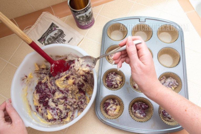 Placing the mix into muffin cups in a muffin tray.