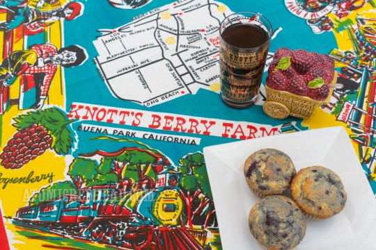 Boysenberry muffins on a plate, which is on a vintage Knott's Berry Farm table cloth, which features a train and a map of Knott's.