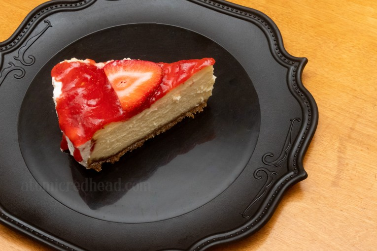 Slice of cheesecake on a black plate.