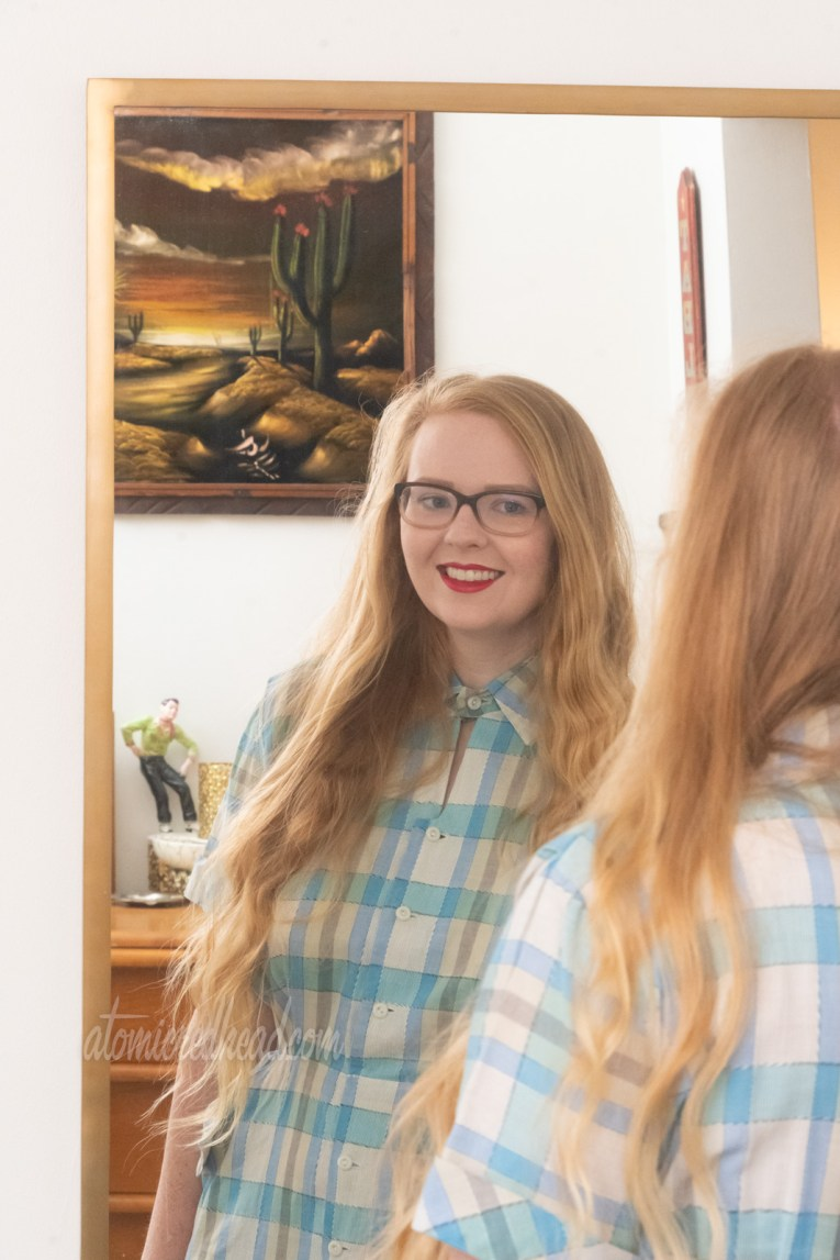 Myself wearing a blue and white plaid dress looking in the mirror.