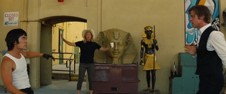 Janet, woman wearing black mock turtle neck short sleeve short, olive capris, and a straw cowboy hat steps in front of a Sphinx head.