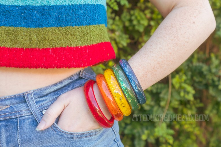 Close-up of my bangles stacked on my wrist, with my hand in my pocket. Red is closest to my pocket, followed by orange, yellow, green, and blue.