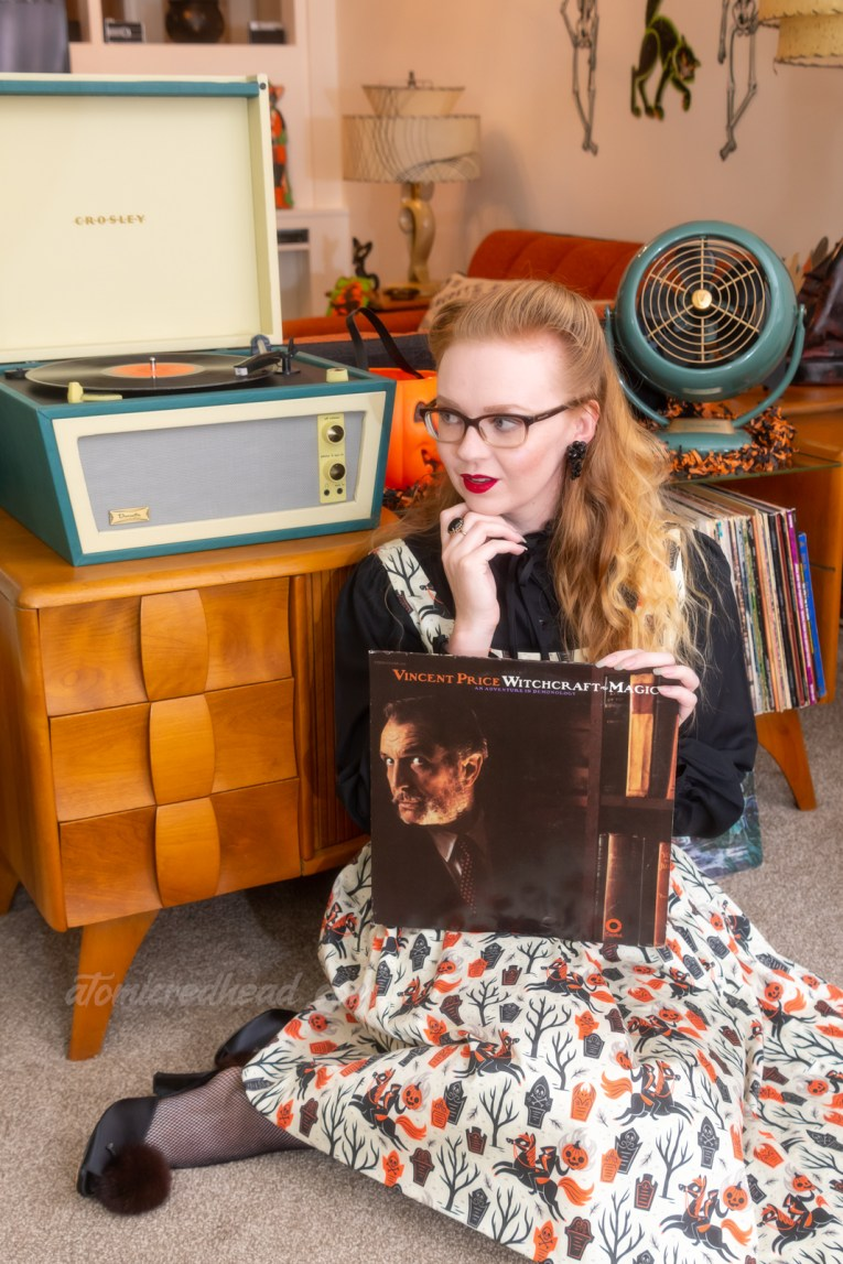Myself wearing a black blouse, under a white dress that features a black and orange print of the Headless Horseman and tombstones, sitting in front of a record player, holding a record featuring Vincent Price.