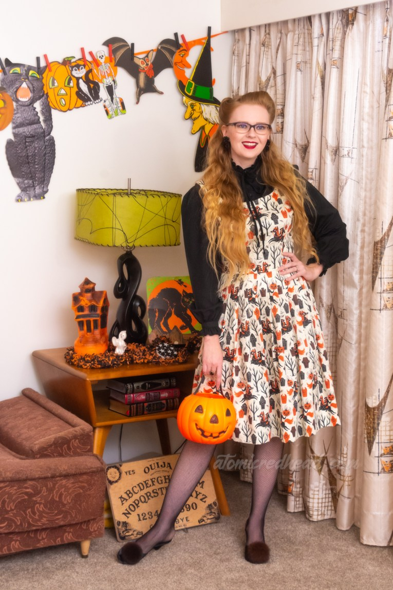 Myself wearing a black blouse, under a white dress that features a black and orange print of the Headless Horseman and tombstones, holding a small plastic jack o'lantern bucket.