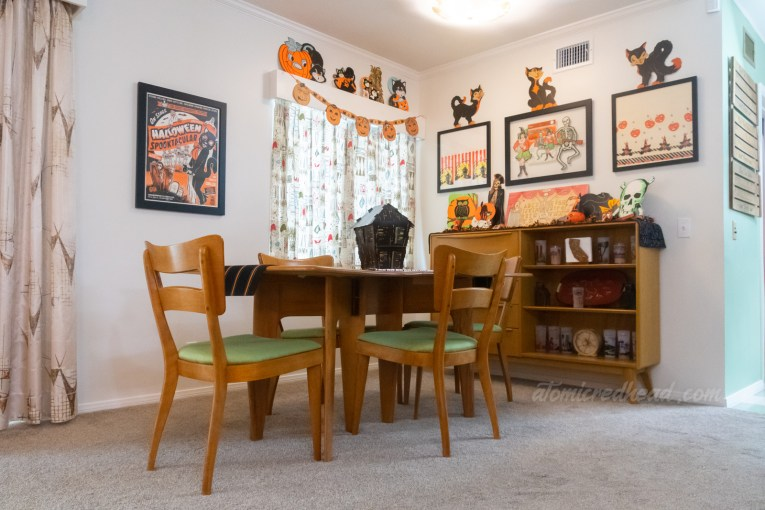 Overall view of the dining room. The dining room table sits in the middle with a 3D paper haunted house in the middle. Hanging to the left is a poster for a Halloween event at Bob Baker Marionette Theatre, a window in the middle, with pumpkins and cats atop the valance, and on the right a buffet with various Halloween decorations.