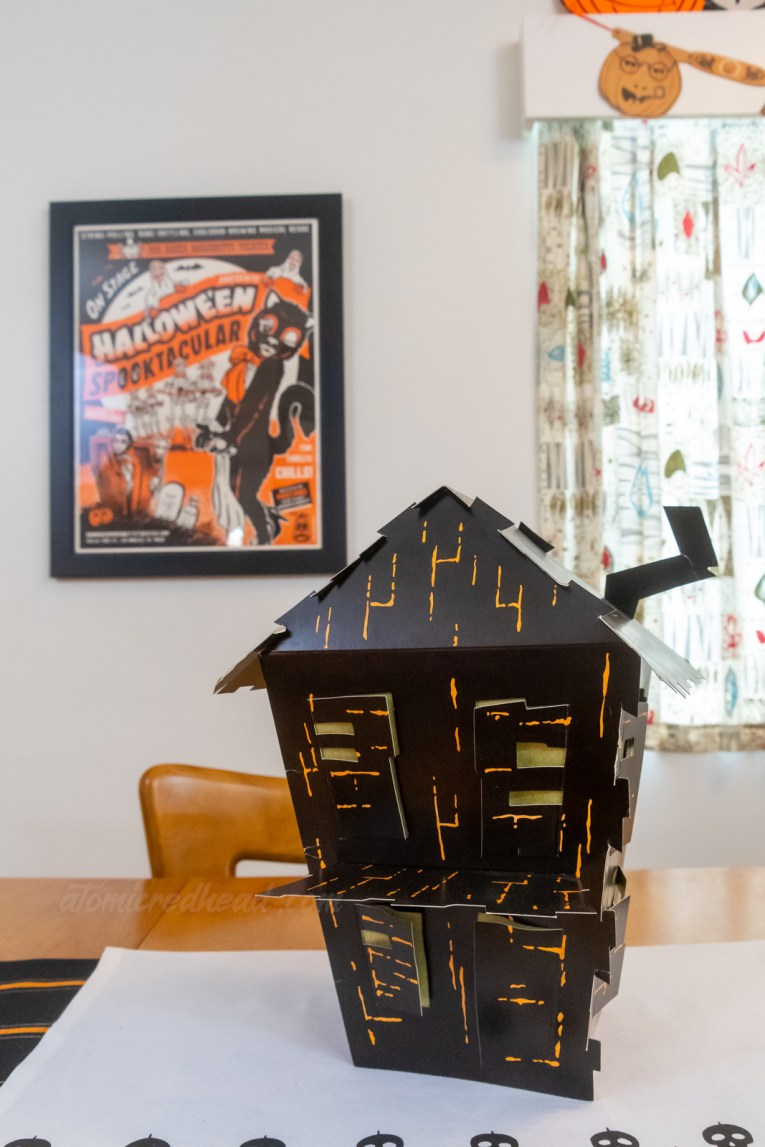 A cardstock haunted house sits in the middle of our dining room table, the poster for the Halloween Spooktacular at Bob Baker Marionette Theatre hangs on the wall in the background.