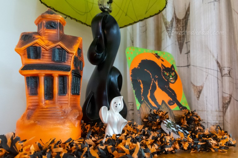 A blow mold haunted house sits atop a table. To the right a small ceramic ghost, and next to it a diecut of a black cat.