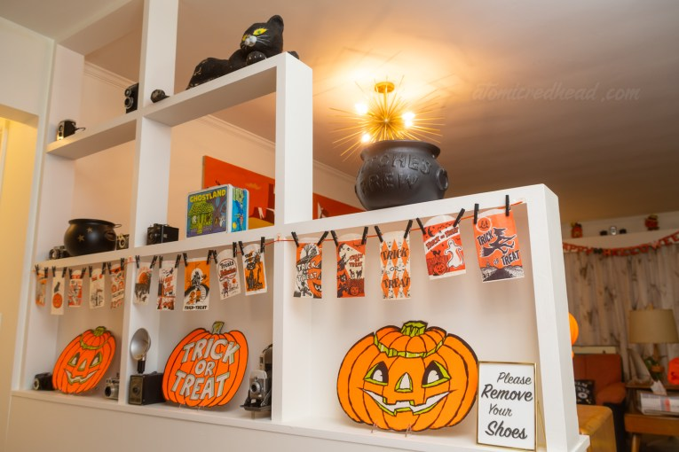 A room divider separates the hallway from the living room. An orange ribbon hangs across part of it and clothes pinned to it are small trick or treat bags. A paper jack o'lantern sits under them.