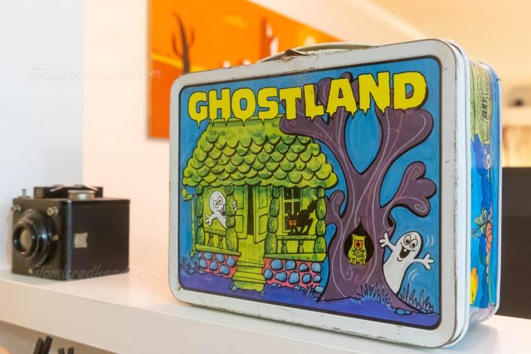 """A metal lunchbox reading """"Ghostland"""" in yellow across the top. A green haunted house has small little white ghosts that pop out."""
