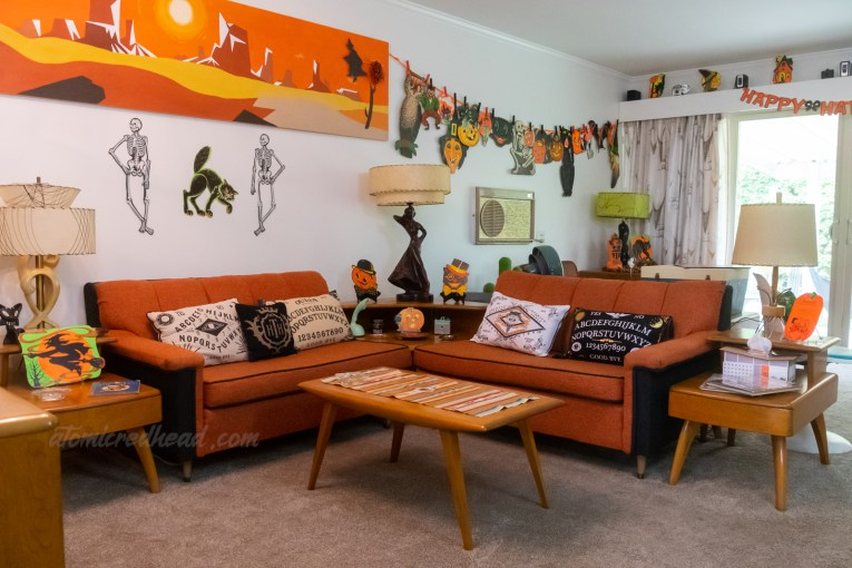 Our orange and black sectional, that sits in the middle of our living room. Behind is a swath of various Halloween decorations hanging on a ribbon. The couch has spirit board print pillows.