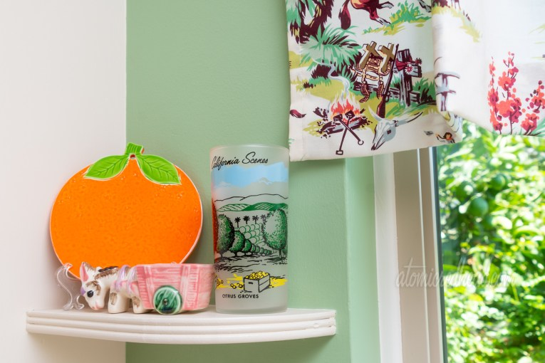 Close-up of one shelf near the sink. An orange shaped trivet leans in the corner, a glass sits next to it featuring a scene of an orange grove, and a small planter of a donkey pulling a cart.