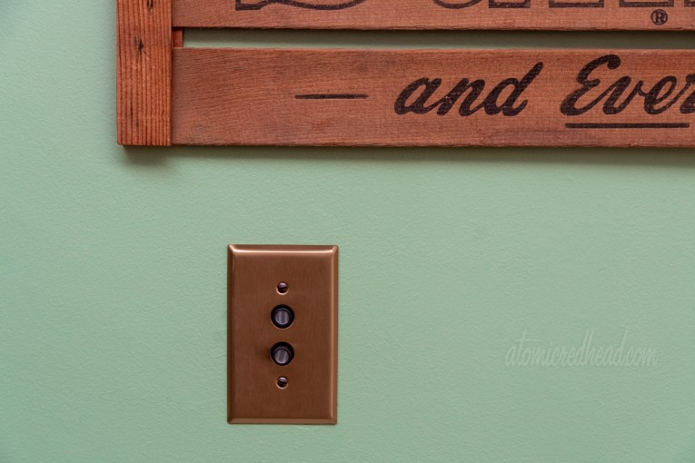 Close-up of our push button light switches, which are surrounded by a copper colored plate.