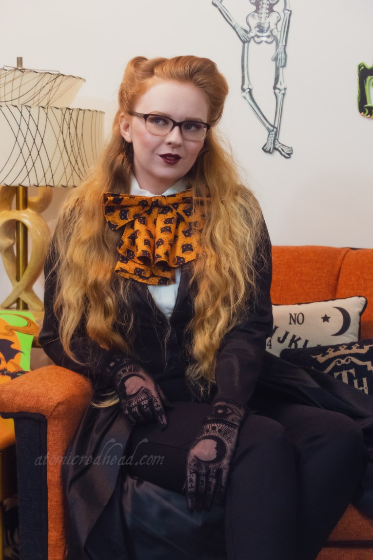 Myself, seated on our orange couch, vintage Halloween decorations hang behind, wearing a black top that features an open skirt, with black cigarette pants underneath. A white blouse peeks out at the top and a large orange bow with a print of black cats is worn at the neck.