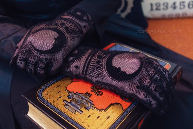Close-up of my gloves, which are black sheer with velvet astrology symbols.