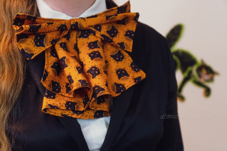 "Close-up of my bow, a large ""pussy bow"" with a print of black cat heads."